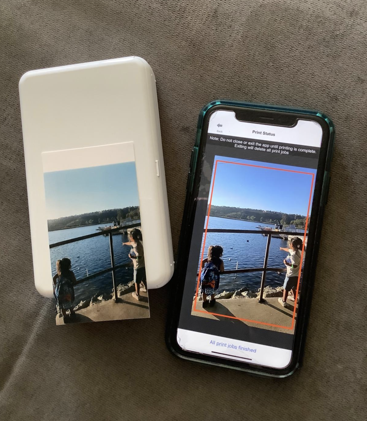 reviewer image of the printer next to a phone with a picture printed out