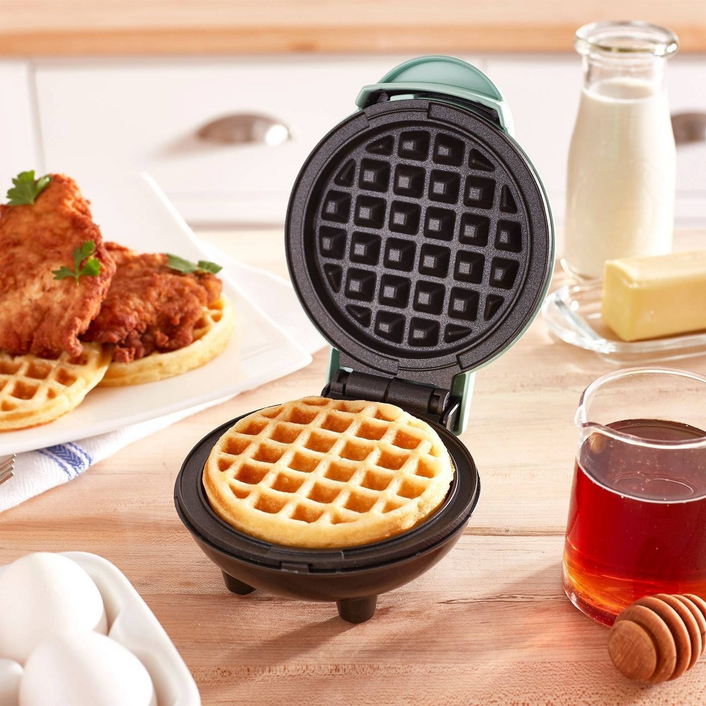 The mini waffle maker opened and finished making a waffle to show its size