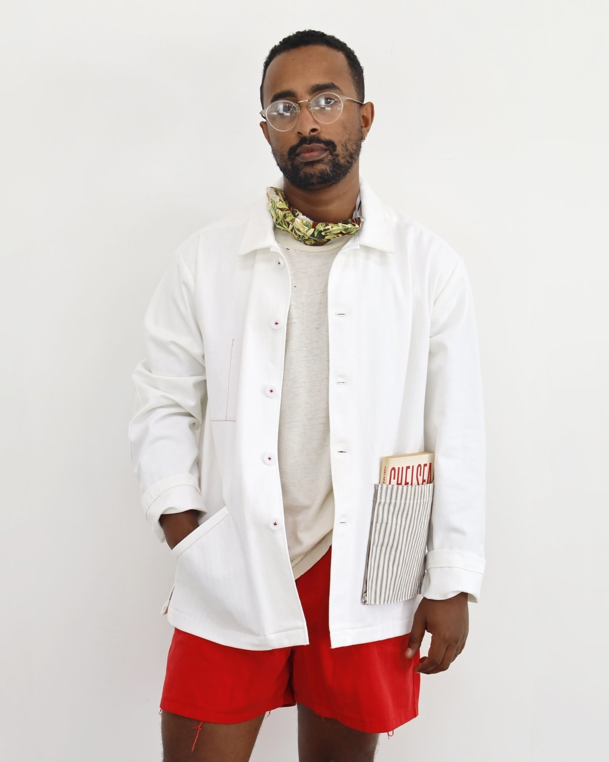 A model in the white jacket with a striped pocket with a book inside, plus other smaller pockets