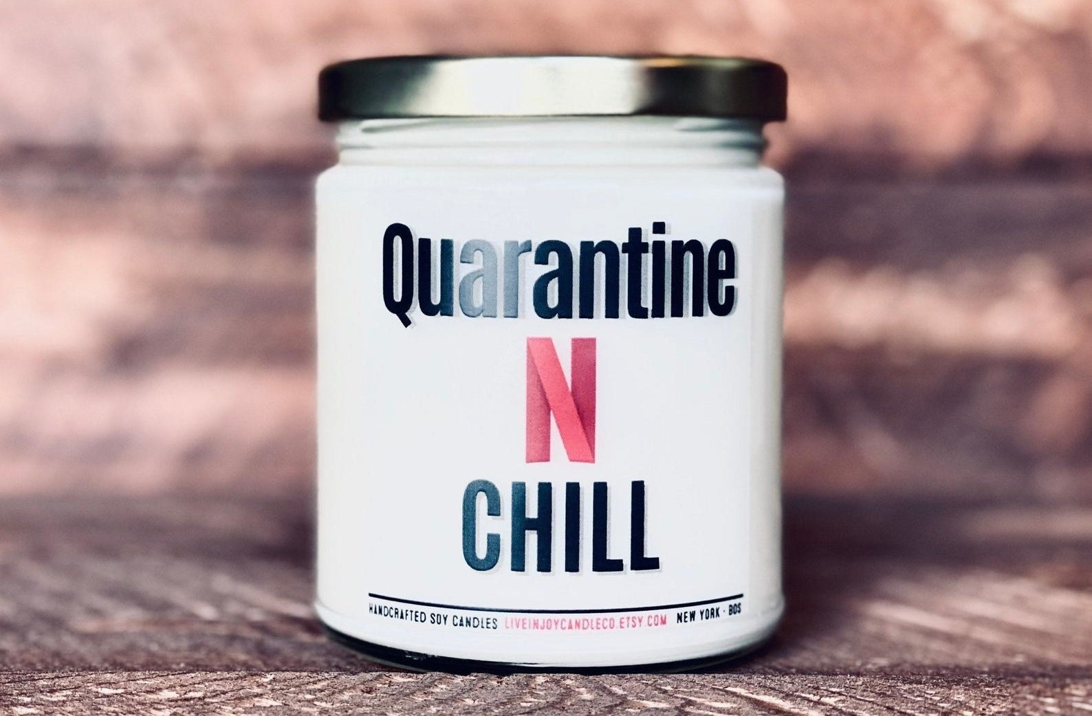 "the candle with the label reading ""quarantine n chill"" on it"