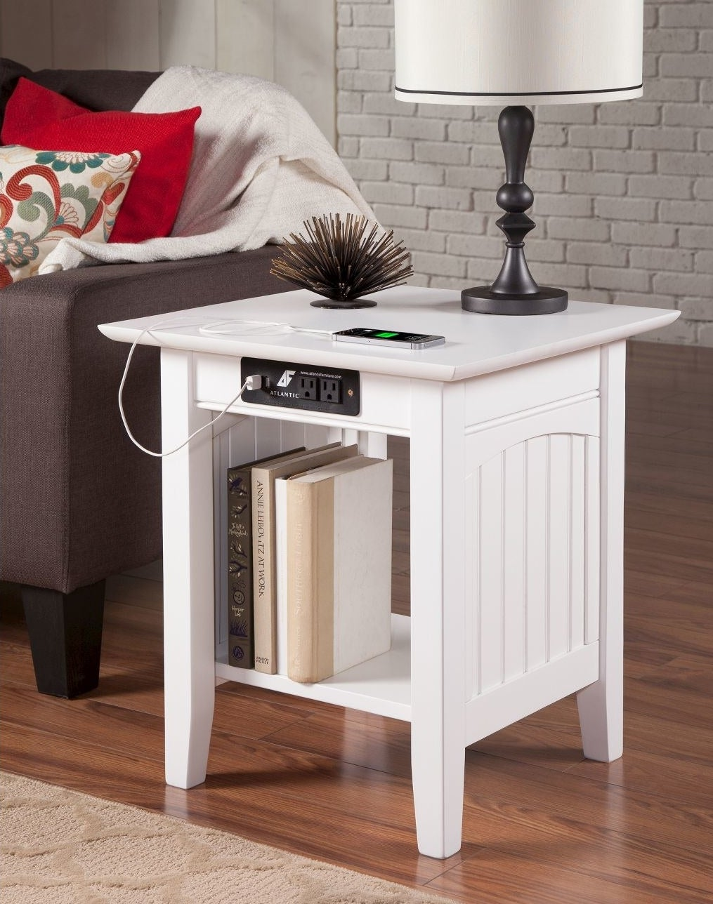 The table in white, which has one large shelf area, and USB and traditional outlets under the rim of the tabletop