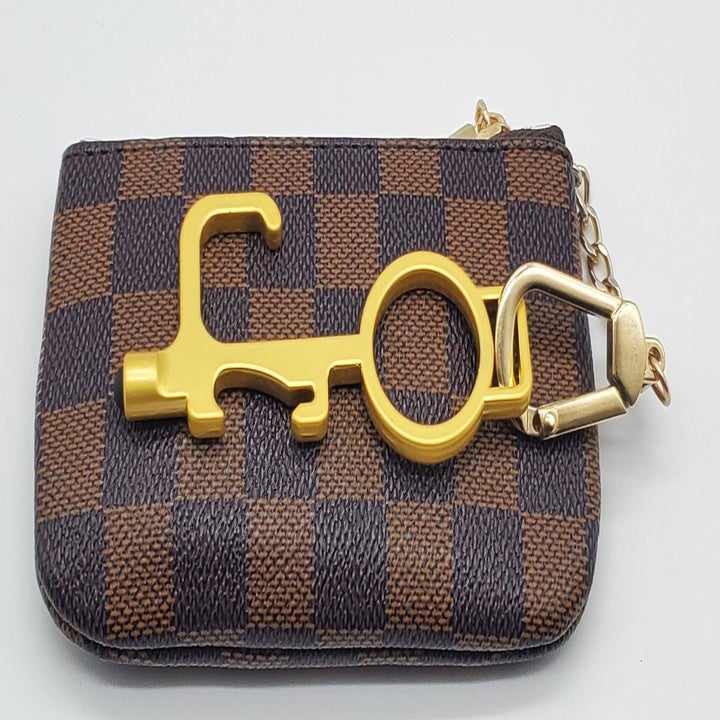 the pusher in gold attached to a keychain on a change purse
