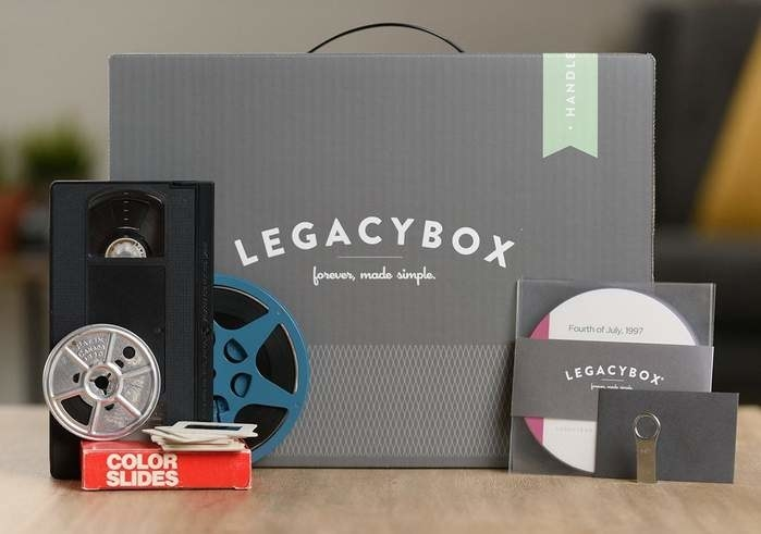 A Legacybox kit alongside color slides, an audio reel, a VHS tape, a DVD, and a thumb drive