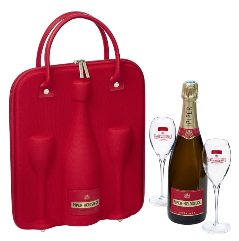 A red travel bag with space for a champagne bottle and two flutes photographed next to an actual champagne bottle and two flutes
