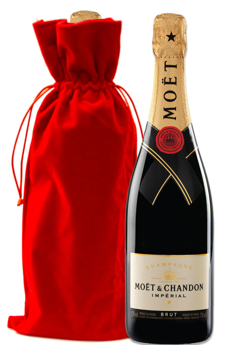 A bottle of champagne photographed next to an upright red velvet gift bag
