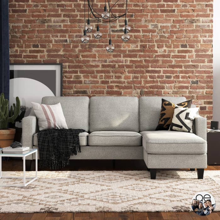 A grey sectional sofa in front of a brick wall