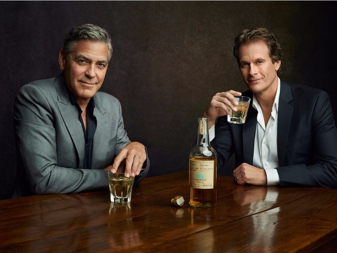 Casamigos founders George Clooney and Rande Gerber sitting at a table drinking glasses of tequila
