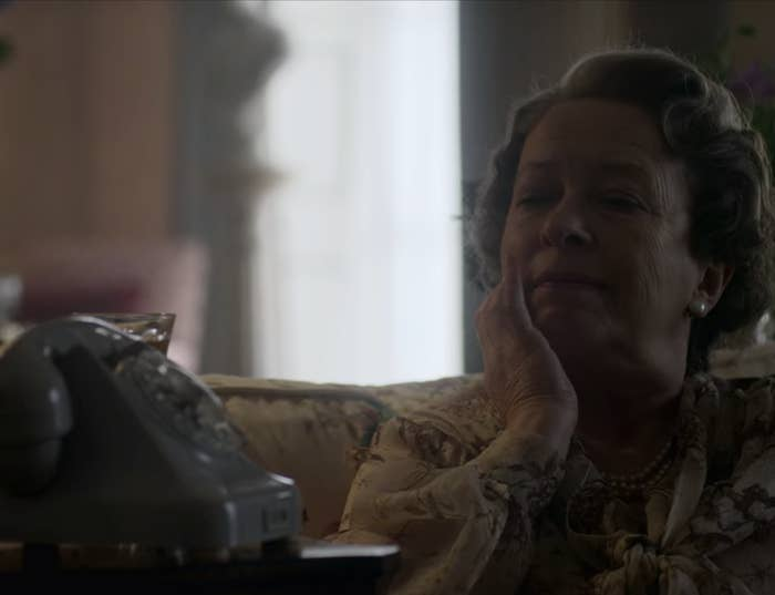The Queen Mother with her hand on her face and she sits on a couch and thinks
