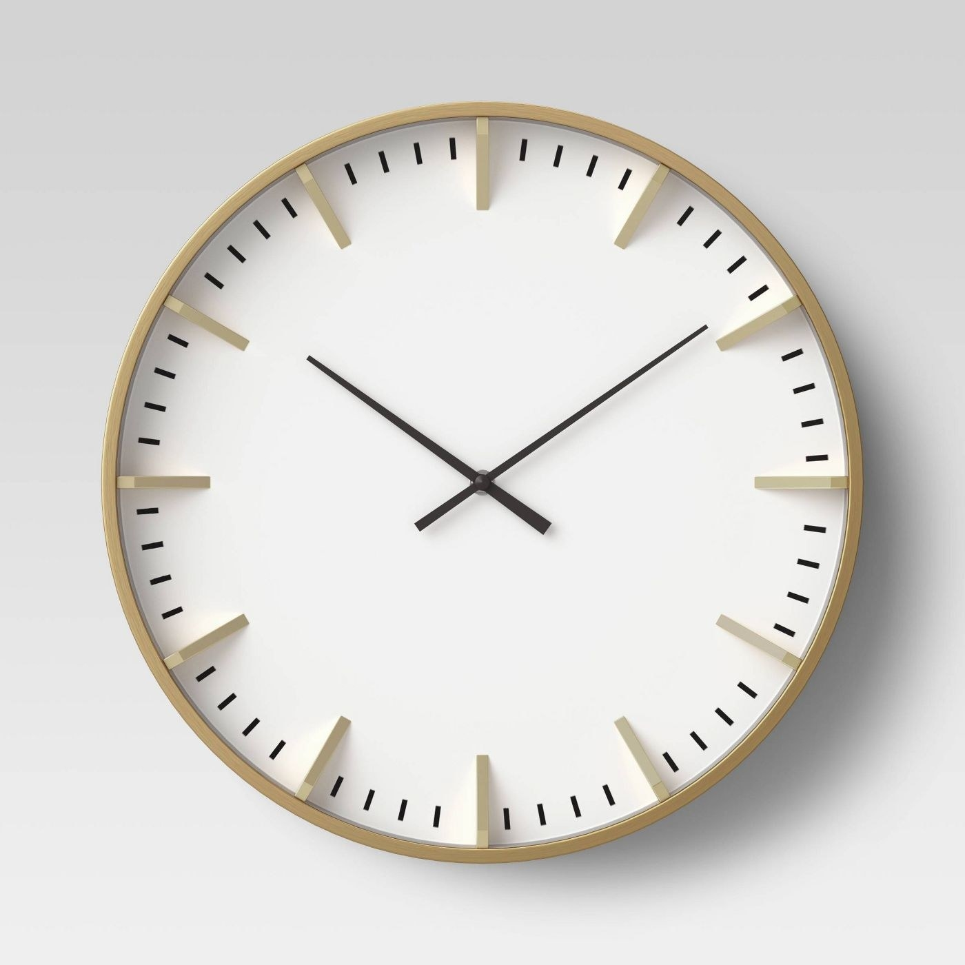 The clock, which is round, with a white, numberless face, and a gold tone outer area