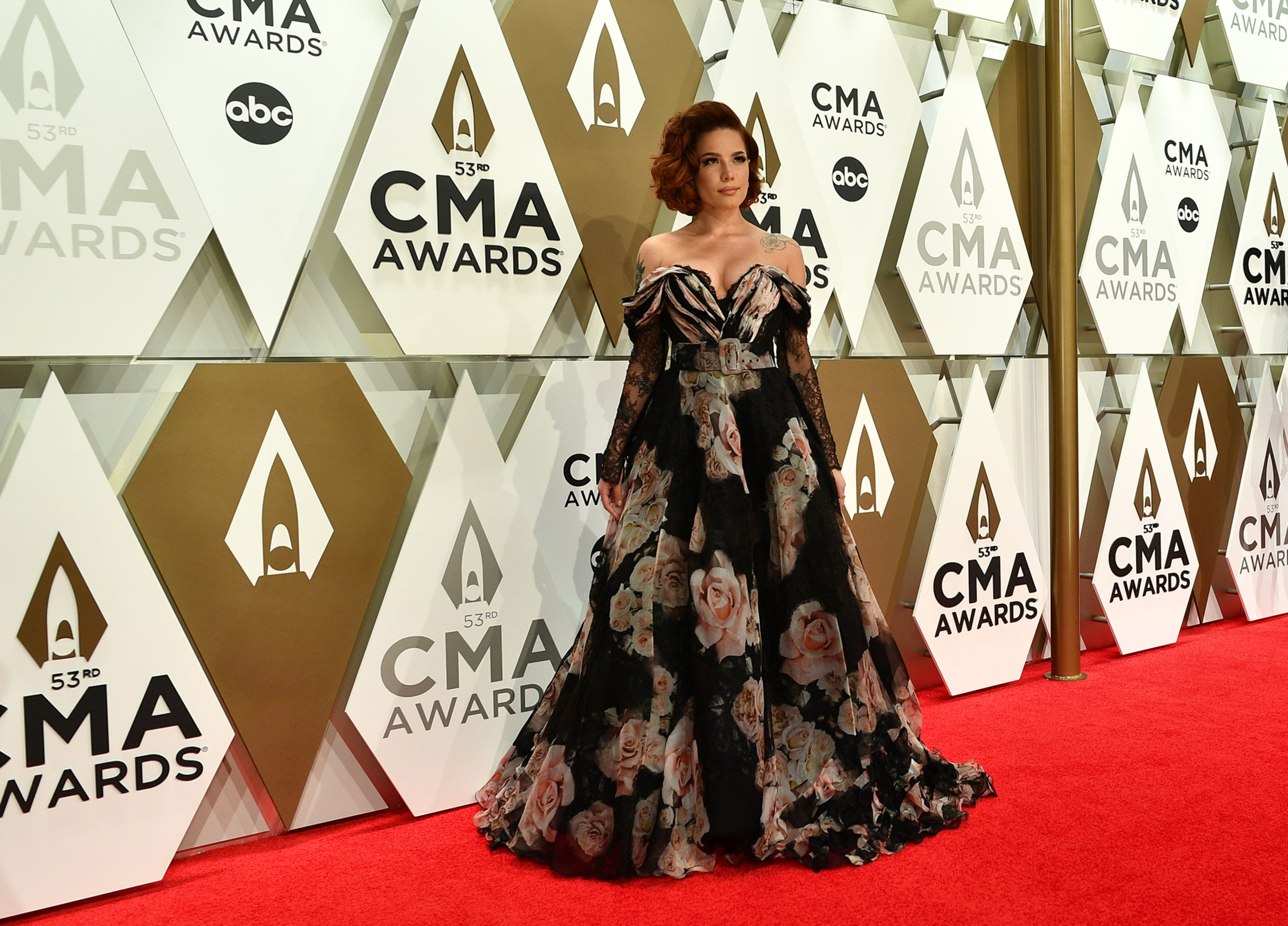 Halsey posing on the red carpet in an off-the-shoulder gown at the 53rd CMA Awards