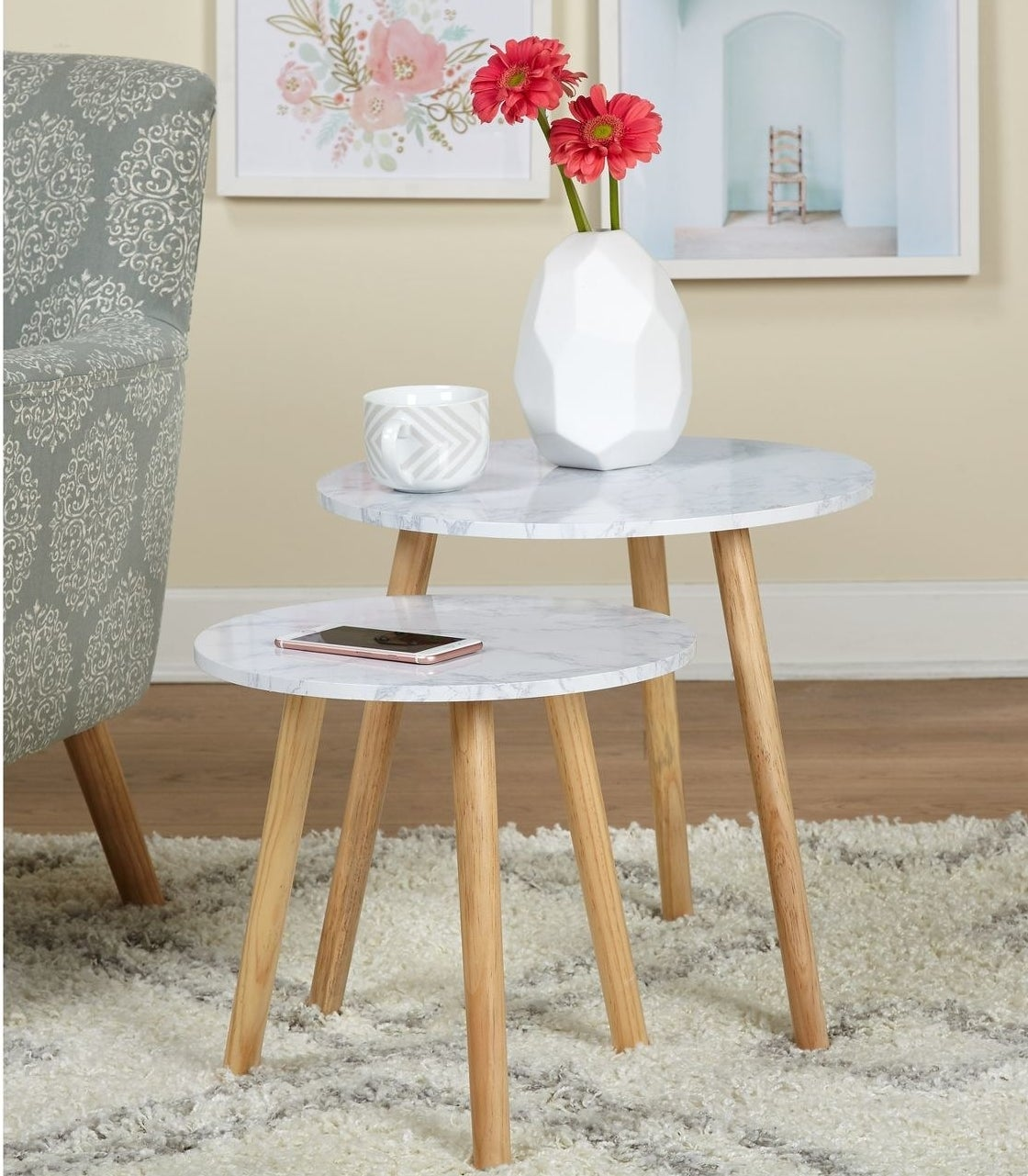 The two tables, both of which have a light gray marble-look rounded top and four wood legs, and one of which is shorter than the other