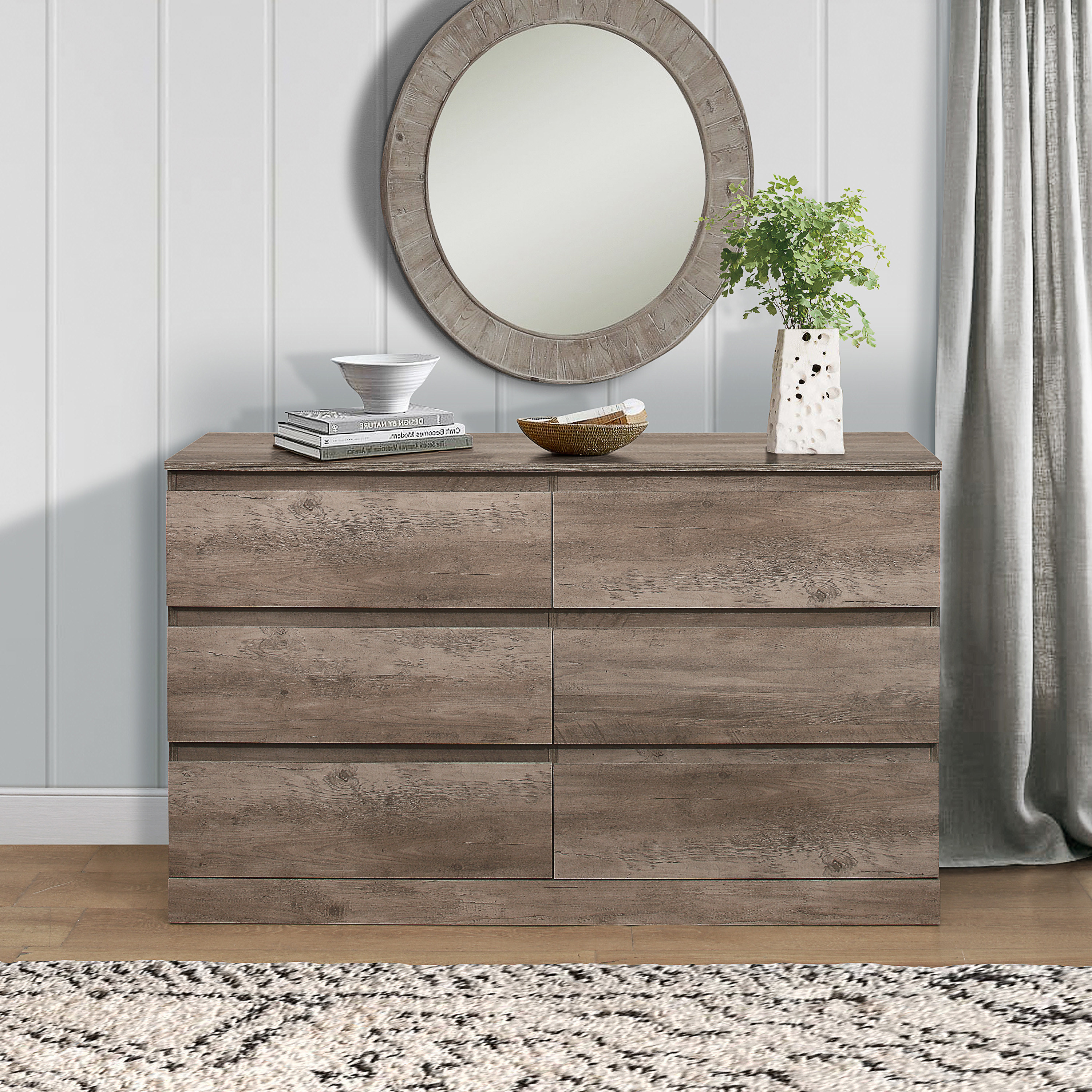 The grey wood dresser with a mirror hanging over it