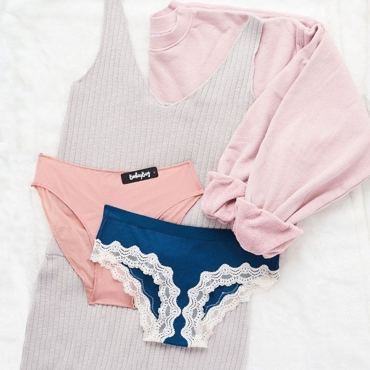 two pairs of underwear, one pink, the other blue with lace trim