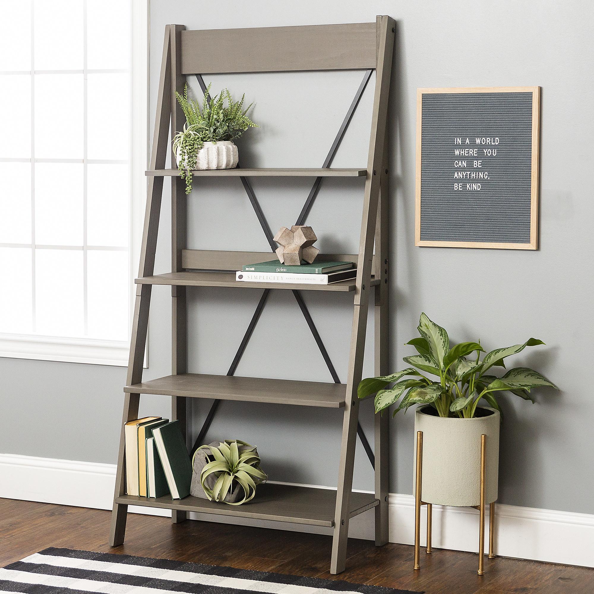 The grey four tiered bookshelf next to a window