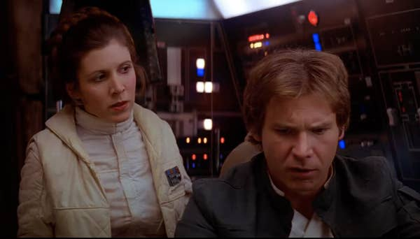 Fisher as Princess Leia looks at Ford as Solo, who looks confused