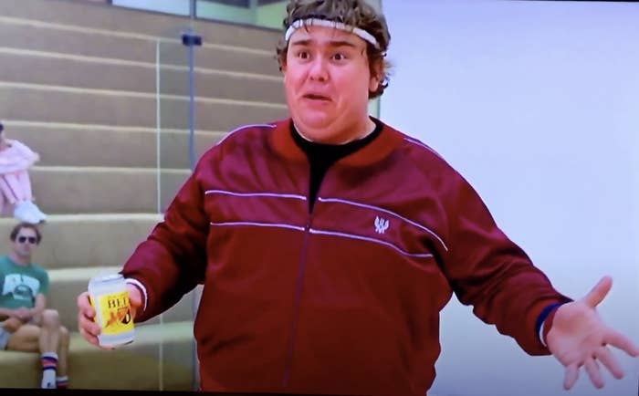 John Candy in workout gear and holding a beer on a racquetball court