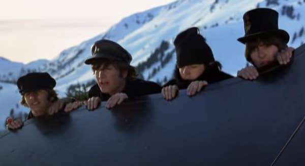 The four Beatles look over a ledge in the snowy alps