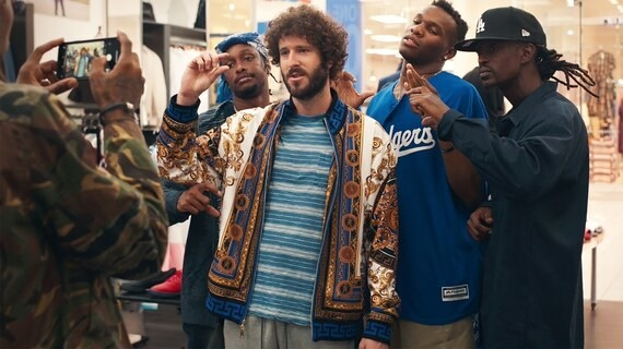 Lil Dicky standing in front of a group of people, shooting a video.