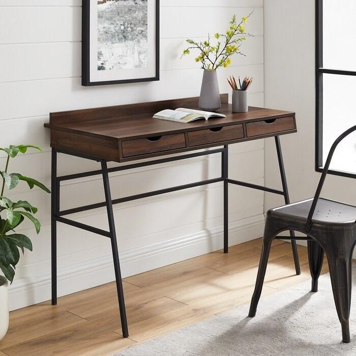 the dark walnut gracie oaks christin desk in a decorated office