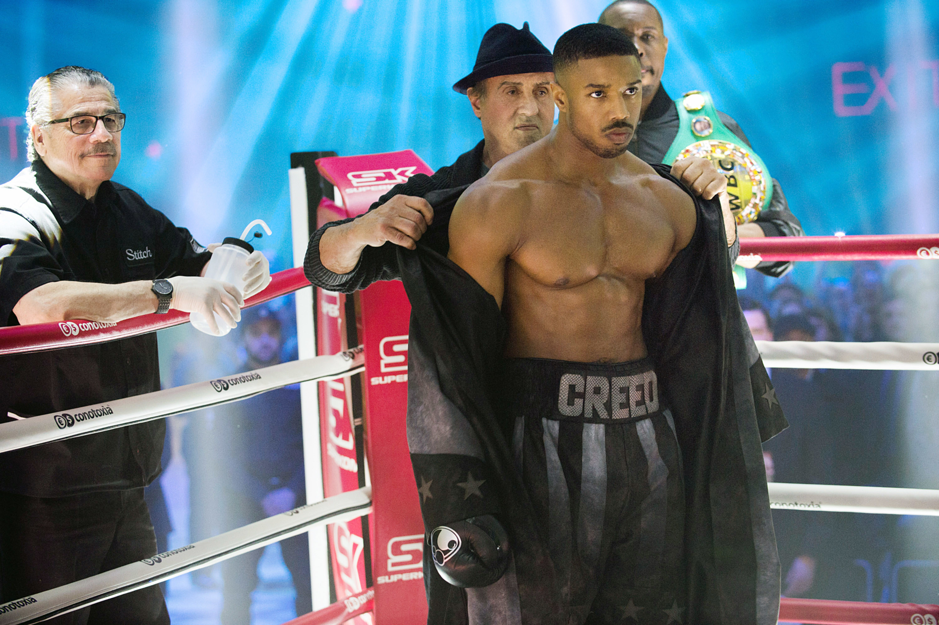Sylvester Stallone as Rocky taking a robe off of Michael as Adonis Creed before he begins a boxing match
