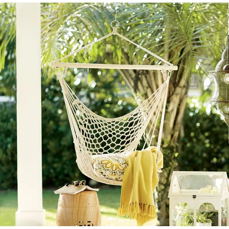 The chair hammock set up outside with a pillow and blanket