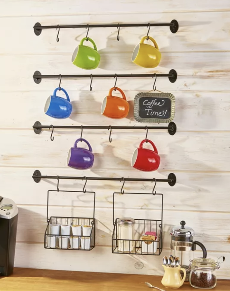 Four metal bars installed on a wall, each with four hooks to hold mugs, plus two small hanging baskets to hold spices