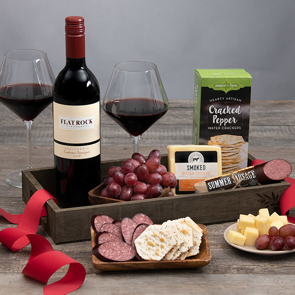 A bottle of wine arranged near an assortments of grapes meats crackers and cheeses