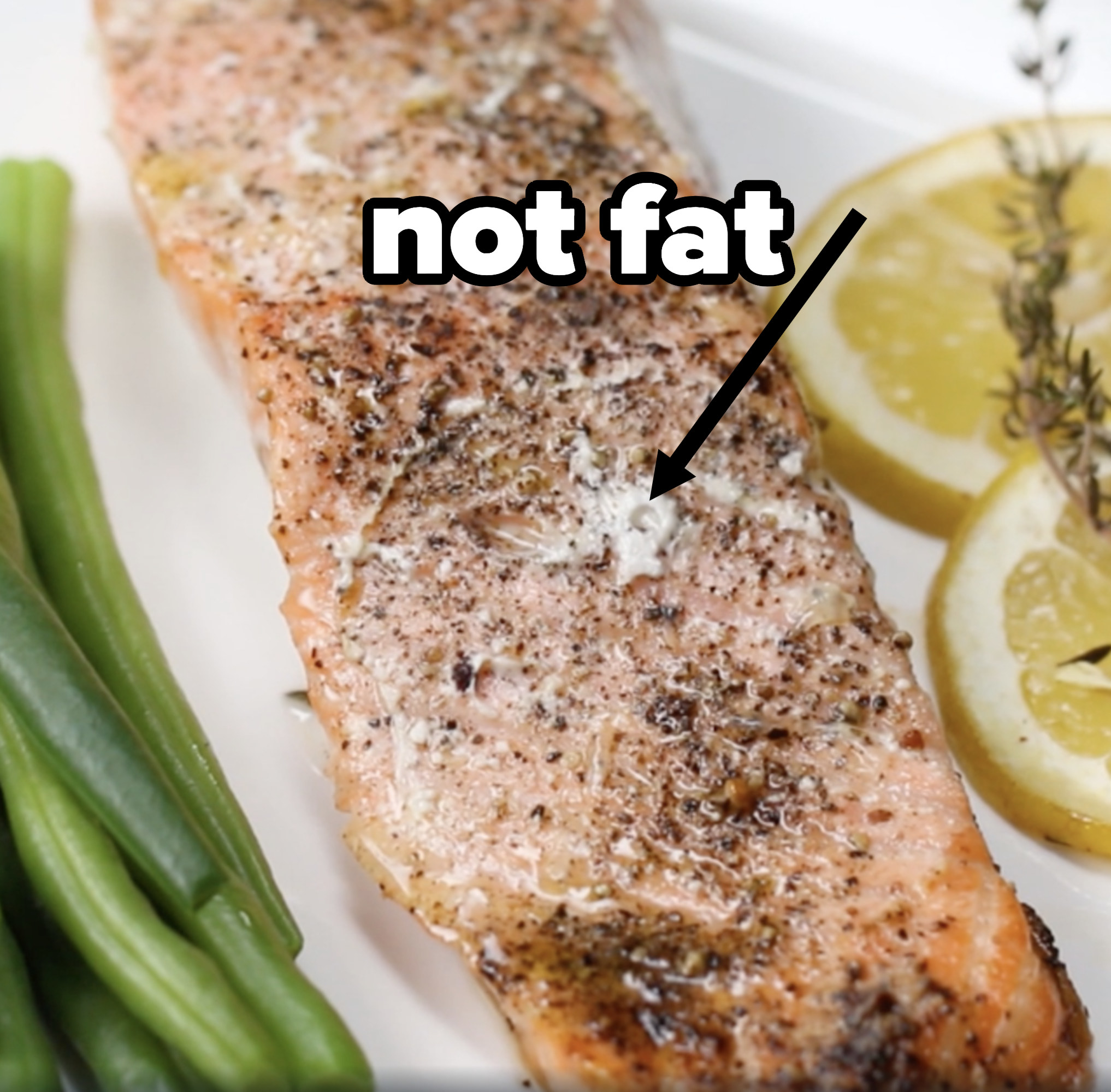 A cooked salmon filet with white gunk visible on top