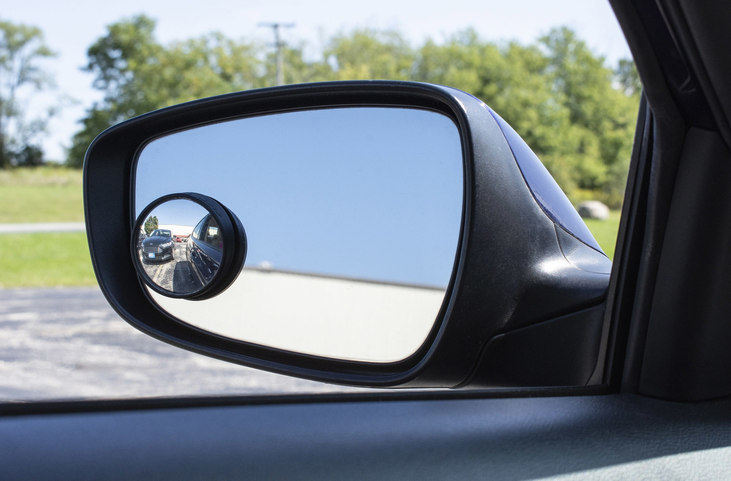 blind spot mirror on a side mirror showing a car in the blind spot