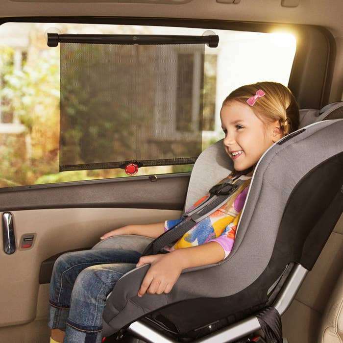 child in a car seat with a sun shade blocking the sun on the window