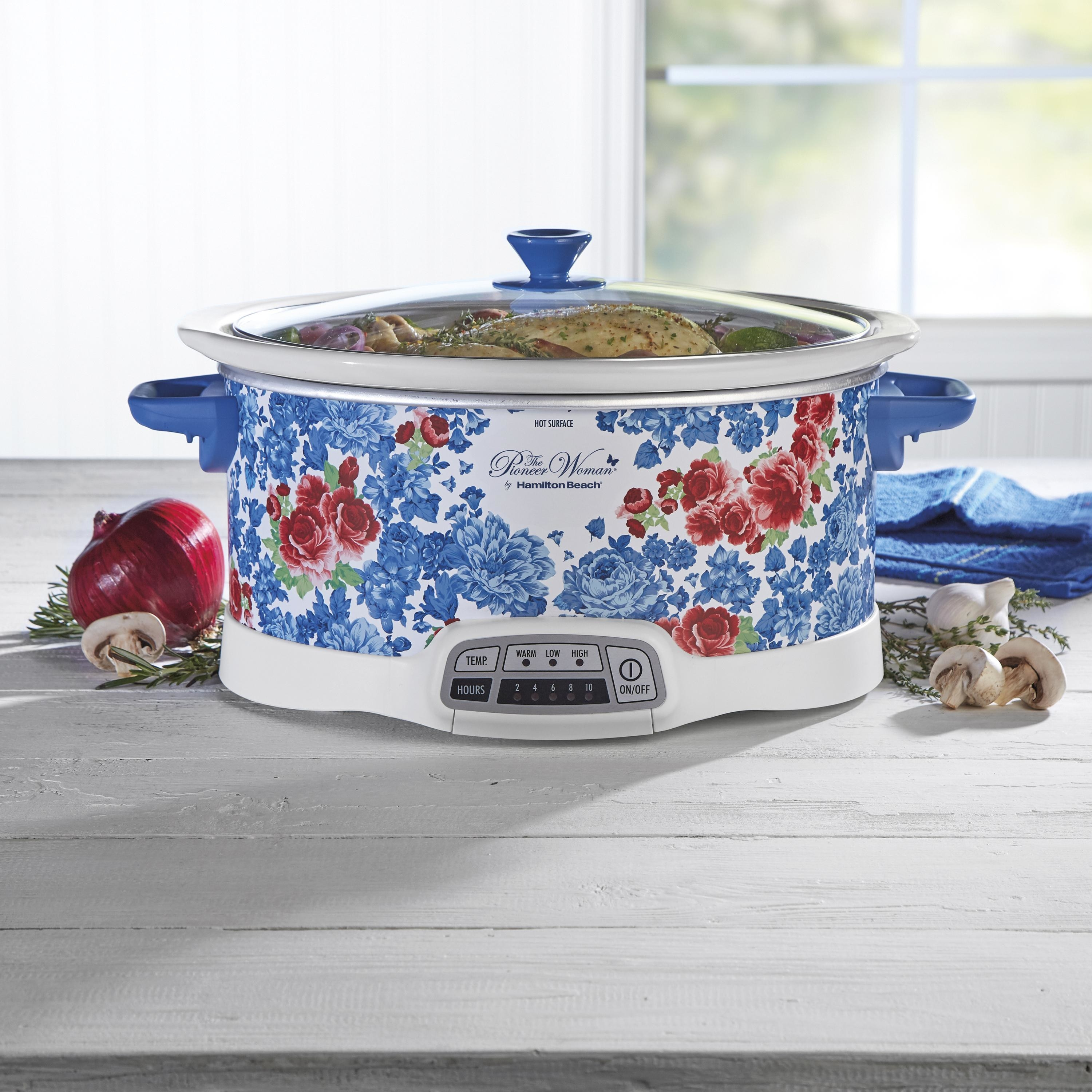a floral patterned slow cooker cooking a chicken with an onion, mushrooms, garlic, and rosemary next to it