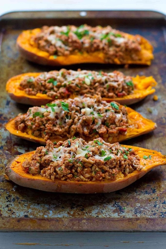 Four halved sweet potatoes topped with ground turkey, cheese, and herbs.