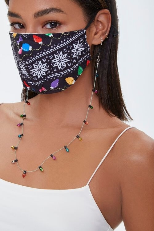 a model wearing the black mask that has white snowflake pattern and colorful lights printed on it with the lights chain