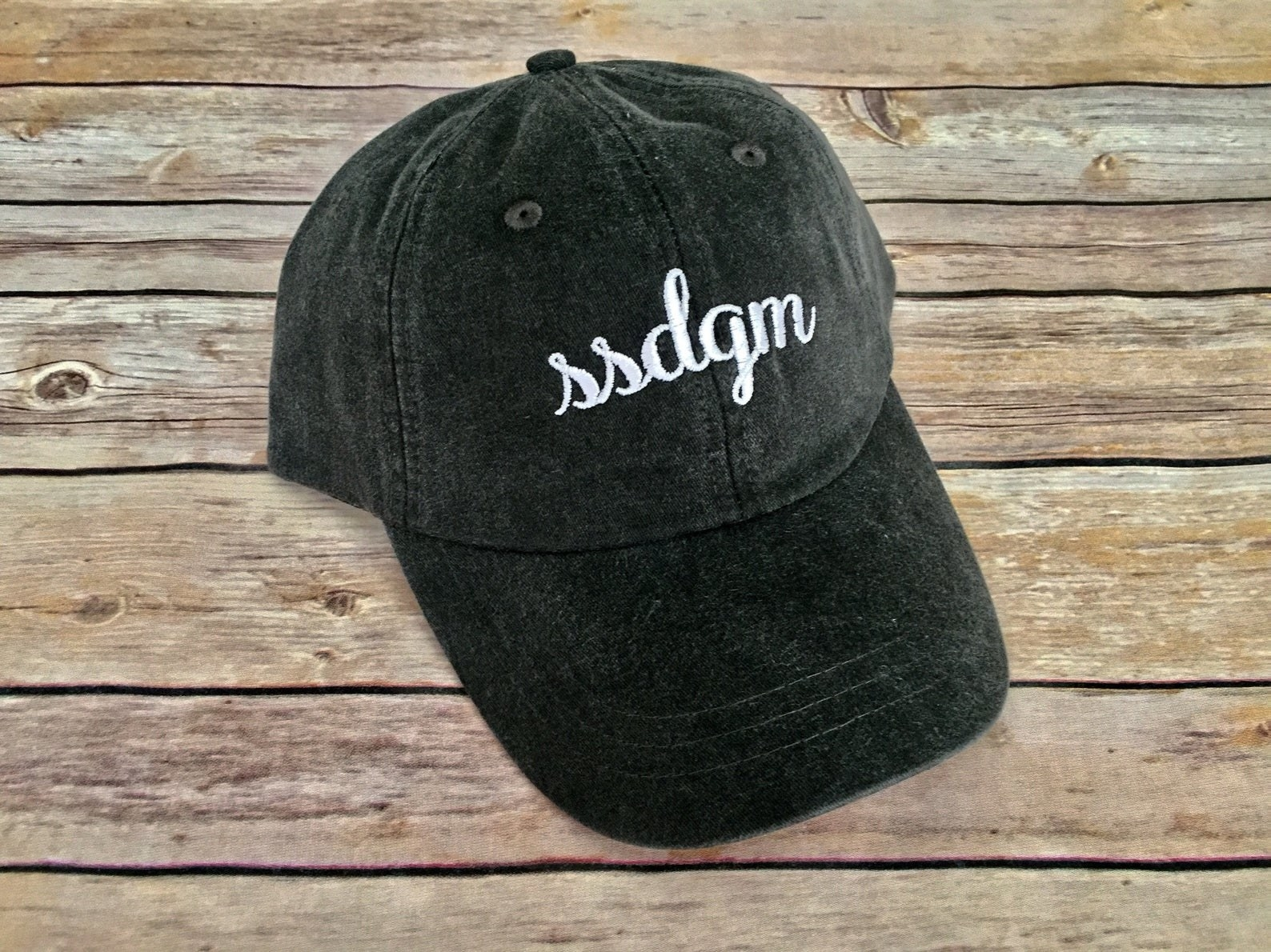 "A black faded baseball cap with white stitching that says ""ssdgm"""