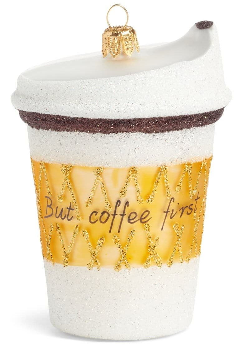 """the white glittery ornament with a gold sleeve print on it that reads """"but coffee first"""""""