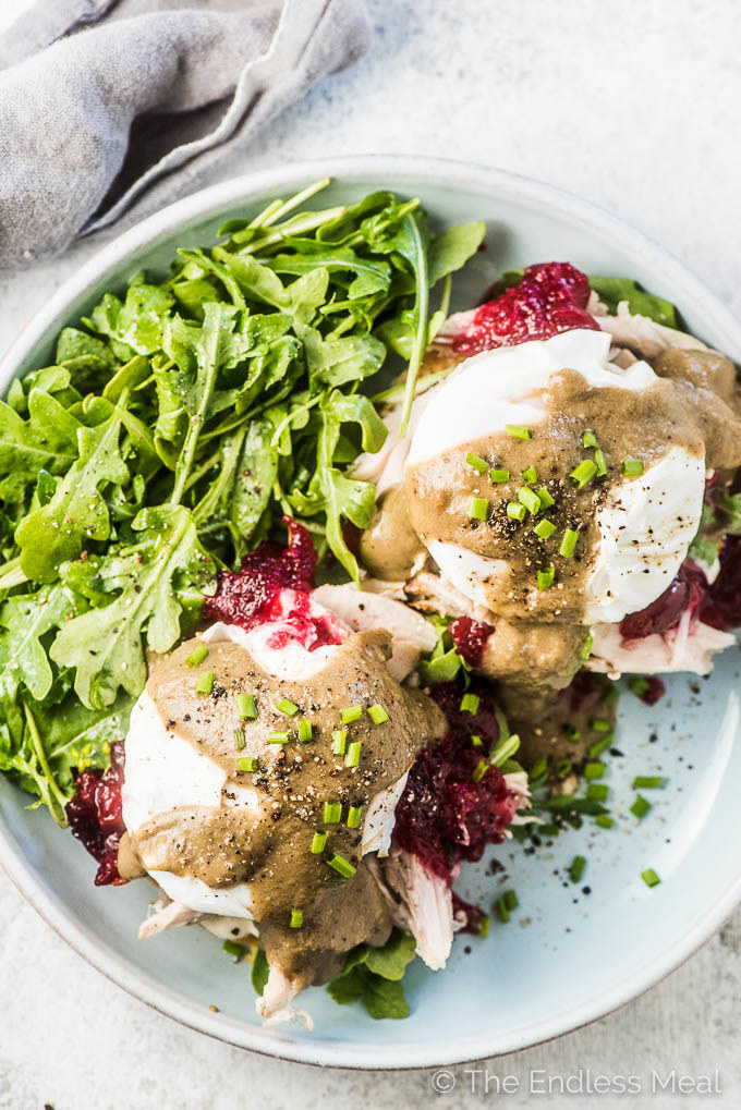 Two poached eggs over turkey breast with cranberry sauce, gravy, and greens on the side.