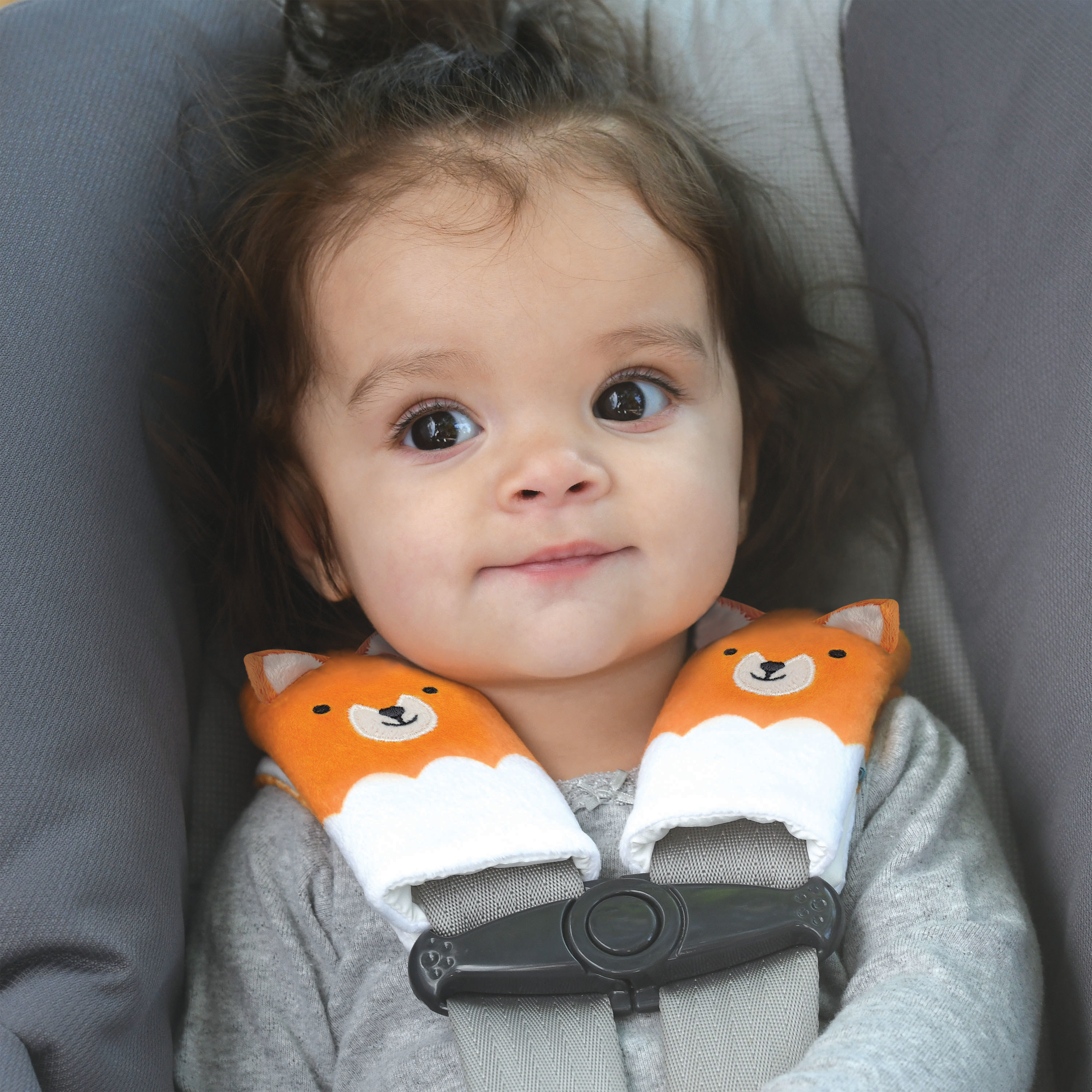 child in a car seat with fox-shaped strap covers on the car seat straps