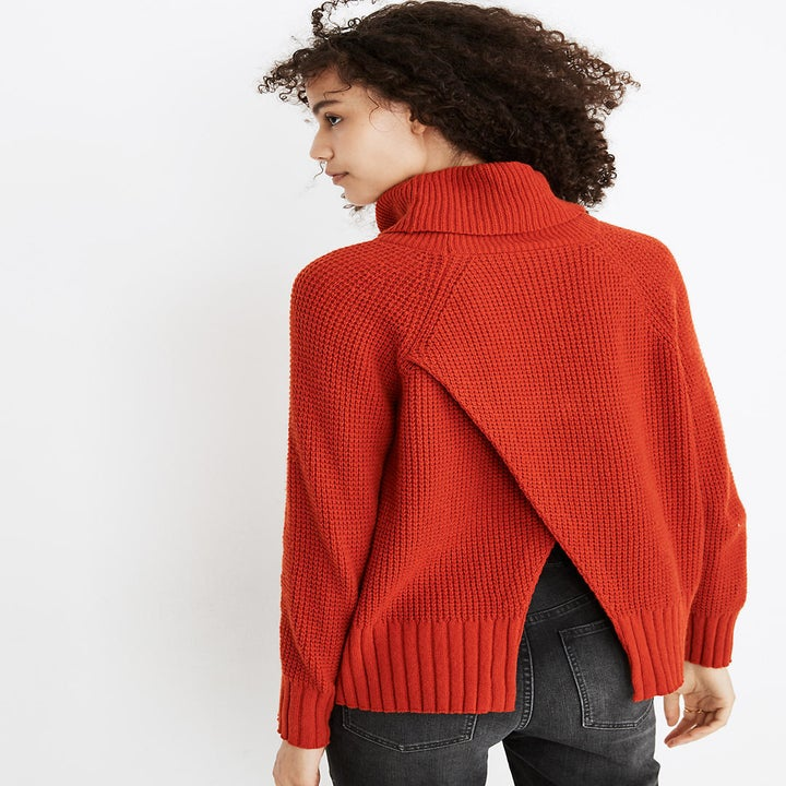 the same model showing the criss crossed design in the back of the red sweater