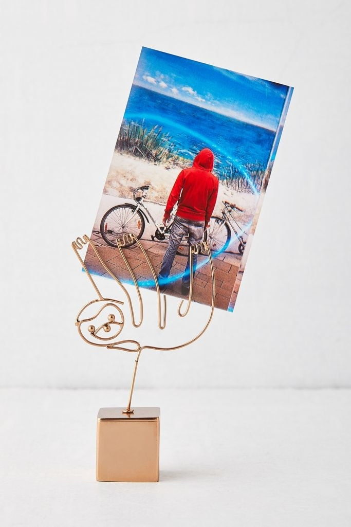 A wire sloth coming out of a cube-shaped platform and holding a printed photo in its arms