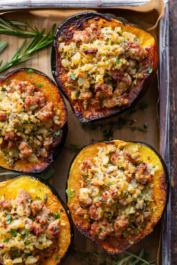 Four halves of acorn squash roasted and stuffed with rice and sausage.
