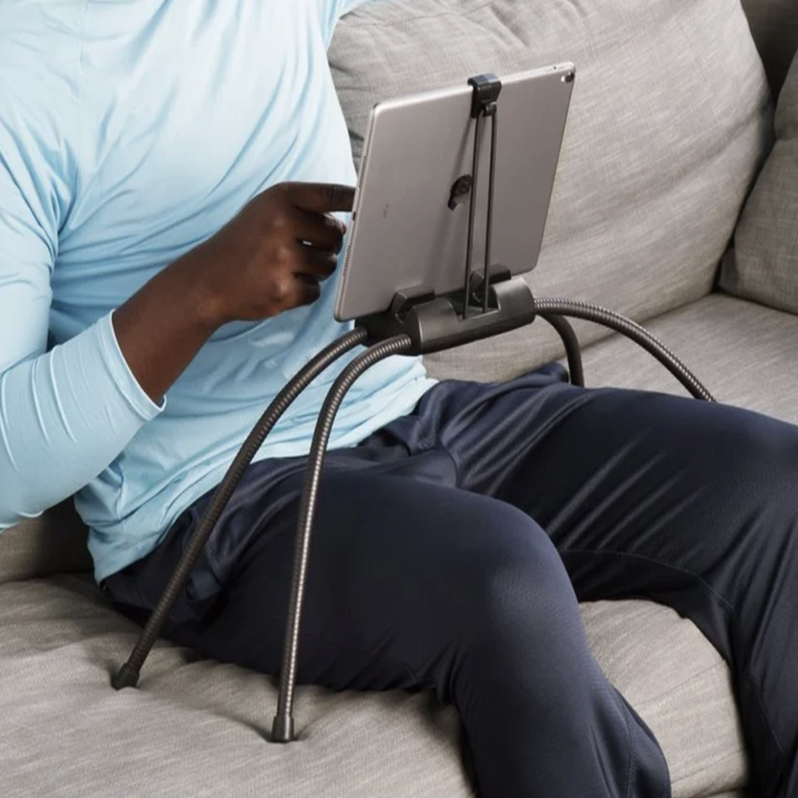 A model using the four legged flexible black stand on a couch with their tablet hovering above their lap