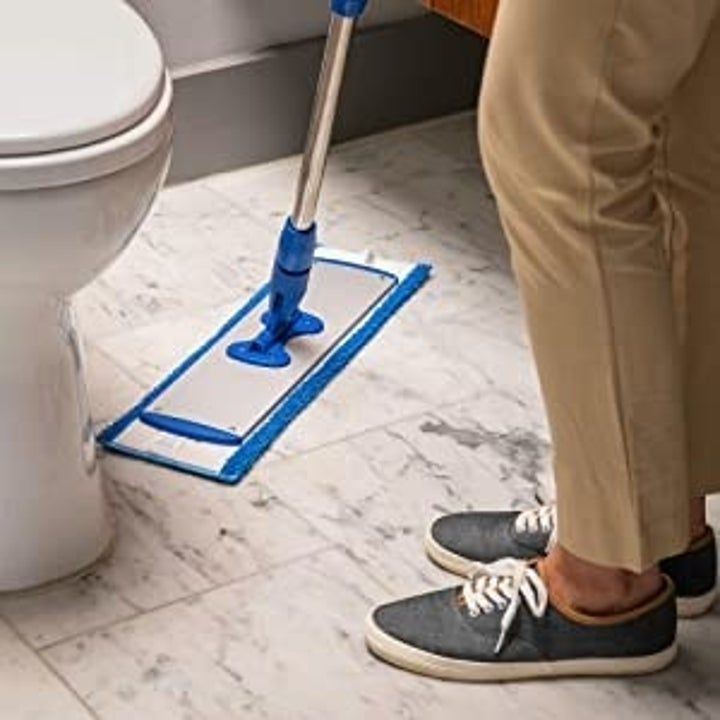 a model using the mop in a bathroom
