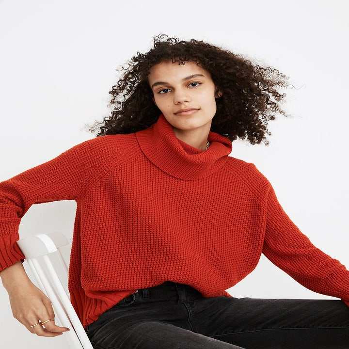 a model in a red cowl neck sweater with waffle knit