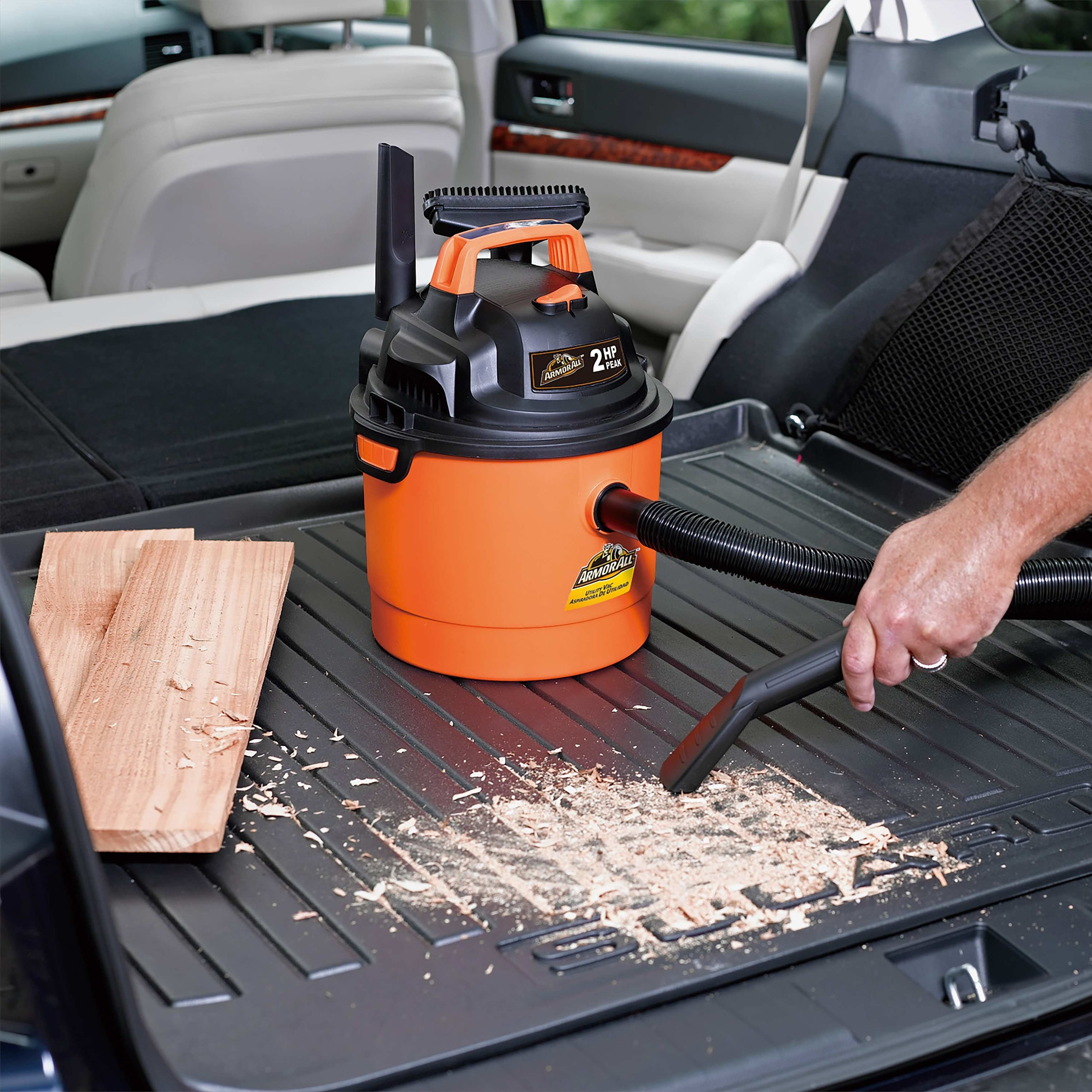 person vacuuming up loose wood chips in their car with a vacuum
