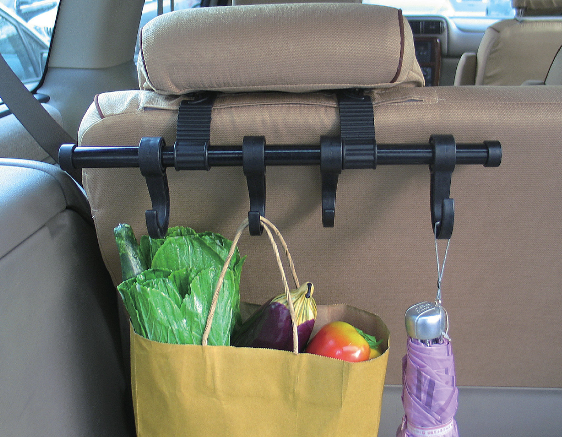 four hook hanger attached to the back of a car seat with a bag and a umbrella hanging off of it