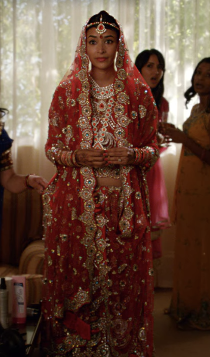 Indian wedding dress with lots of metallic embroidering and a veil that goes over