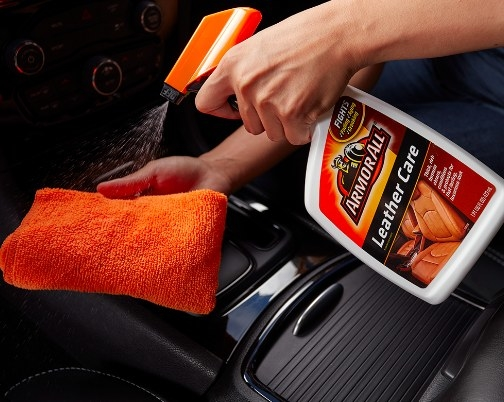 person spraying armor all leather care cleaner on a orange microfiber cloth