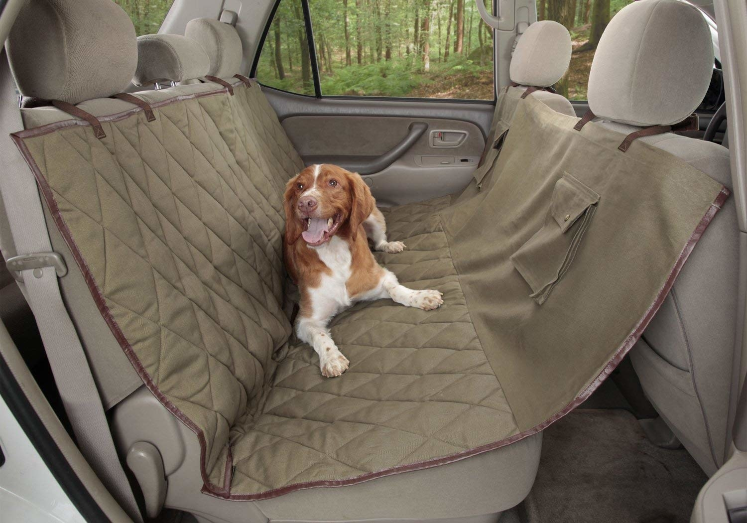 dog sitting on a back seat cover in a car