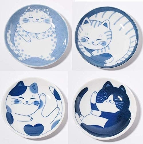 Four blue and white plates with cat illustrations