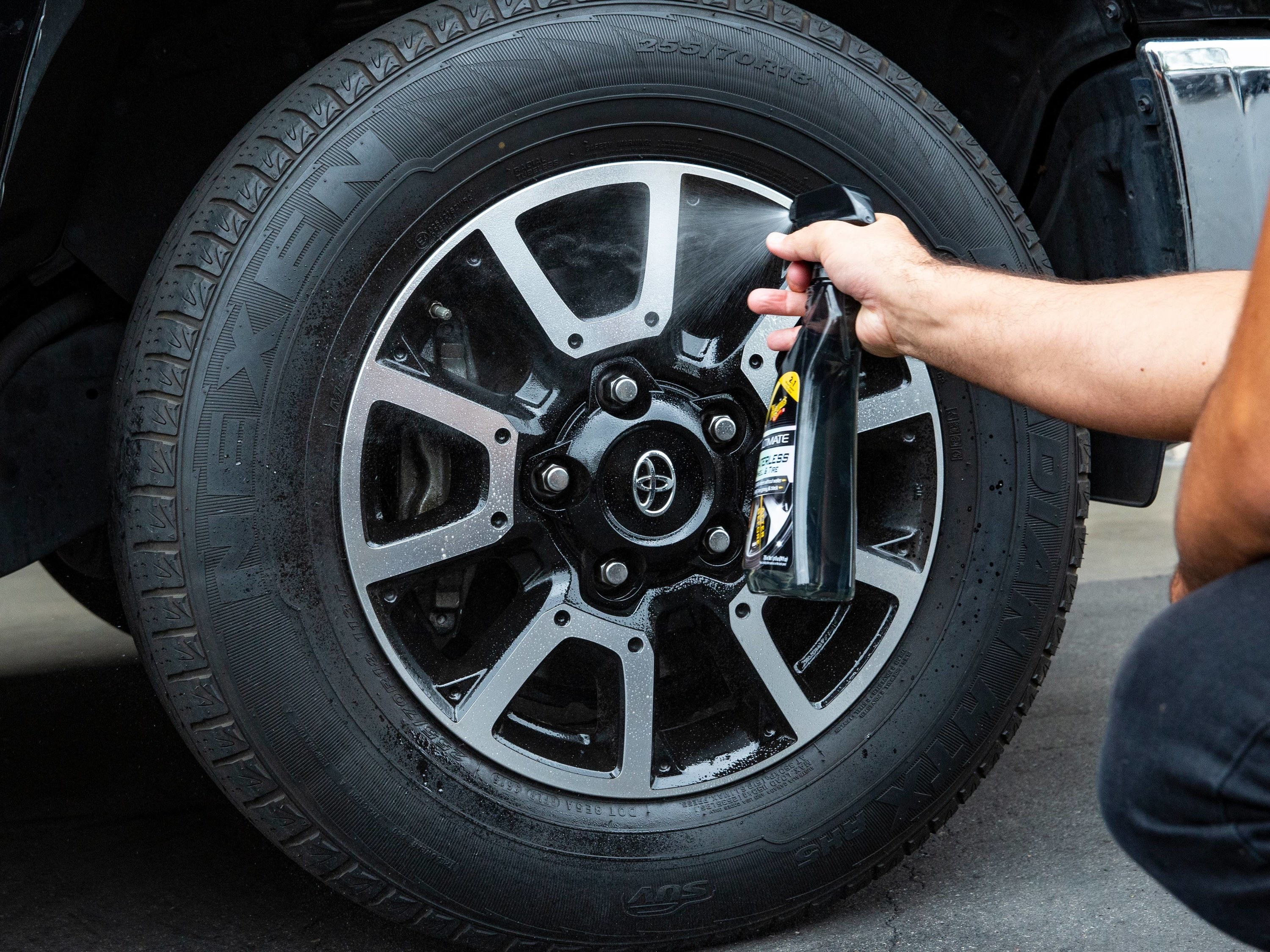 person spraying a wheel and tire dressing cleaner